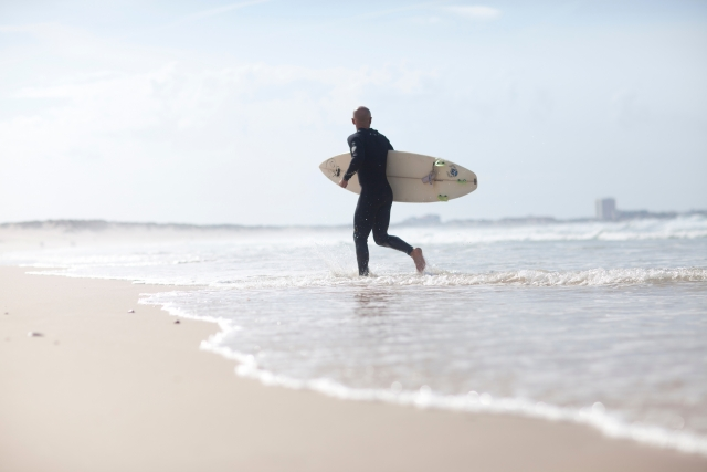 海岸でサーフボードを持っている人