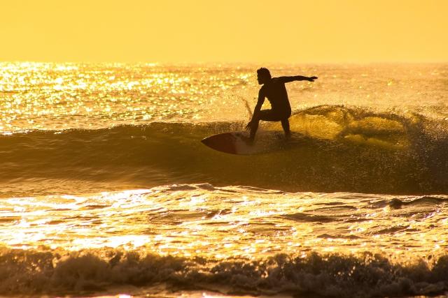 綺麗な夕日でサーフィンを楽しむ人