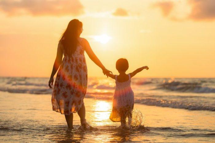 夕方の海岸で手を繋ぐ母親と子供