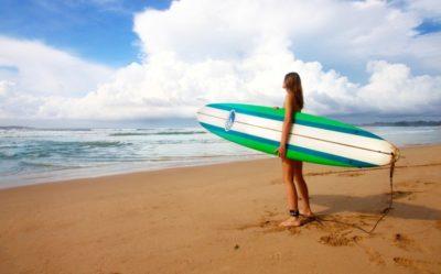 サーフボードを持って海にいる女性